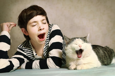 woman and cat yawning